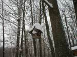 Bird house laden with snow