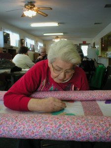Myrna Atkinson hand stitching the butterfly quilt