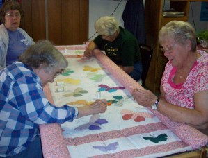 Stitch and Chat Quilters working on handmade butterfly quilt