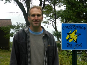 Ryan Conner proudly stands next to his Conservation Star Home Award sign
