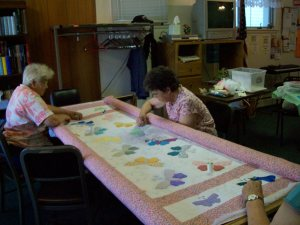 Myrna Atkinson and Carol Hubin quilting the butterfly pattern