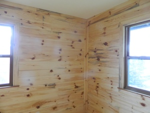 Knotty pine bedroom with red pine walls and floor