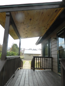 Front porch. Knotty pine ceiling. Ramp on one side and steps on the other.